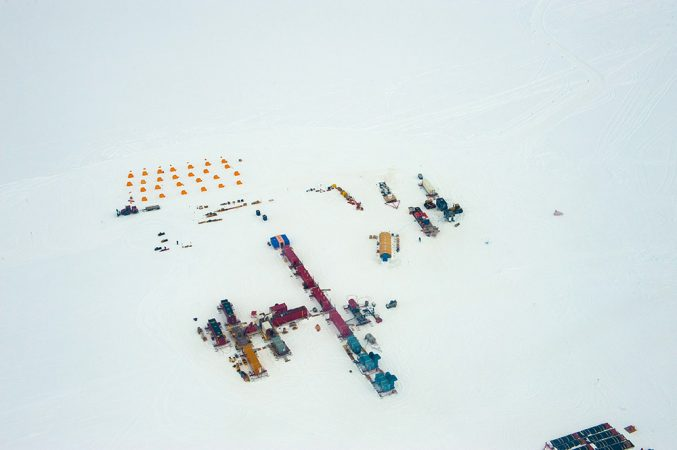 The drilling camp at Lake Whillans covered two acres. But it seems small amid Antarctica's vast ice sheet. People working at the camp stayed in 28 small yellow tents laid out in rows (author Douglas Fox slept in the second tent from the right in the front row; photographer JT Thomas slept in the tent in the back-right corner). A row of seven red and blue sleds holds most of the drill machinery. The blue, red and yellow sleds to its right contain portable laboratories. Credit: © JT Thomas