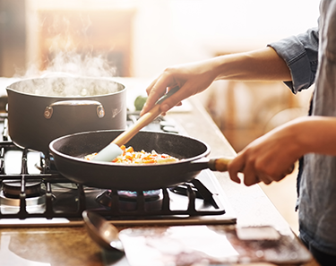 a photo of hands cooking with a frying pan on a stovetop