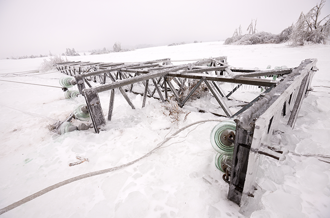 a photo of a power pole downed by an ice storm