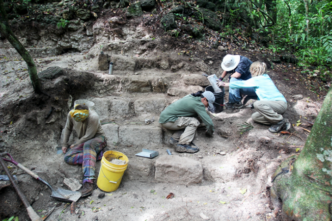 a photo of archaeologists and volunteers working to excavate an archaelogical site
