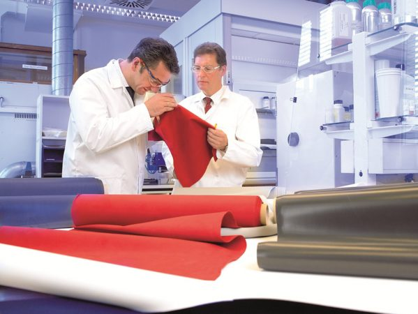 Thomas Michaelis, left, examines a textile sample as part of his work for Bayer AG. As head of textile coatings, he helped design clothing known as Techfit. This coated fabric clings tightly to the body but stretches and moves with a player's muscles. Credit: Courtesy of Thomas Michaelis