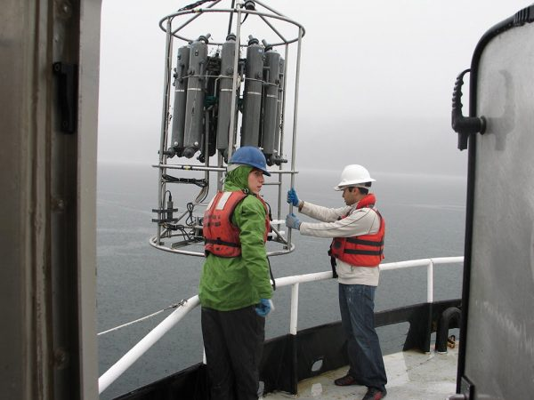 Scientists on a research ship prepare to lower an instrument, called a CTD rosette, into the ocean. The rosette, lowered on a cable, can sample water at different depths in the ocean, starting near the surface and going down thousands of feet. Water sampled this way allows scientists to discover microbes that grow deep down in the ocean. Credit: David Stahl (University of Washington)