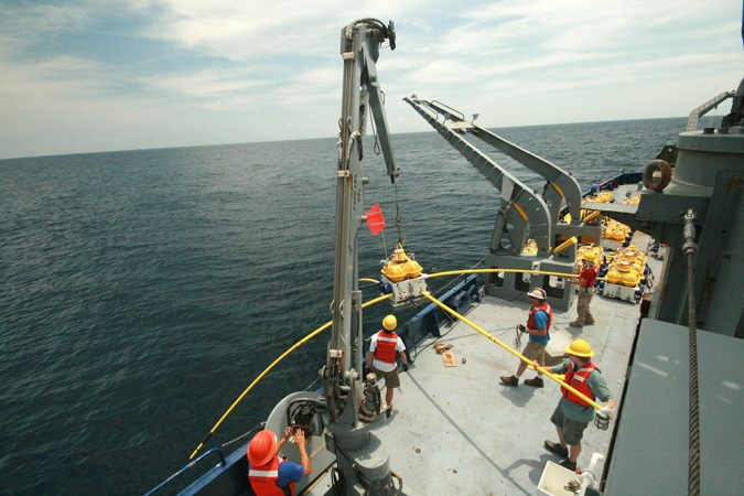 Scientists prepare to lower sensing equipment onto the Pacific Ocean floor. The equipment measured the seafloor rock's ability to conduct electricity. They ran these tests at sites where one plate slides under another. Credit: Kerry Key, Scripps Institution of Oceanography at UC San Diego