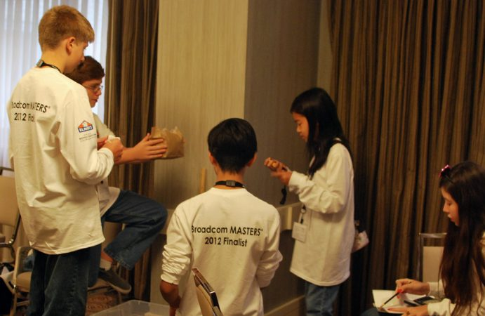Students on the White Team — one of six at the 2012 Broadcom MASTERS competition — participate in the egg drop challenge. This group used packing peanuts and bubble wrap to try to protect a raw egg in a brown paper bag from cracking when dropped. Credit: