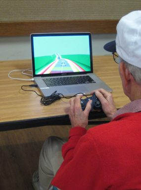 Older man plays NeuroRacer. With practice, it will improve his performance on the game and on mental tests of memory and attention, new data show. Credit: The Gazzaley Lab