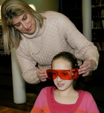 Researcher Mariana Figueiro of Rensselaer Polytechnic Inst. helps a middle school student test a pair of orange goggles in an early study showing the connection between sleep problems and lack of exposure to morning light. Credit: Lab of Mariana Figueiro/ RPI