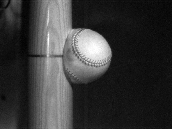 When a bat hits the ball, it can briefly deform the ball. Some of this energy that went into squeezing the ball will also be released to the air as heat. Credit: UMass Lowell Baseball Research Center