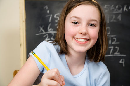 a girl holding a pencil and smiling in front of a chalkboard full of math problems