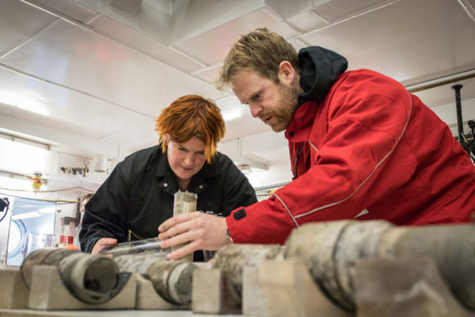 researchers with a sediment core