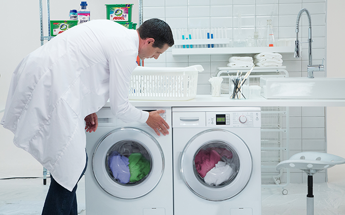 A man in a lab coat bending over to do laundry
