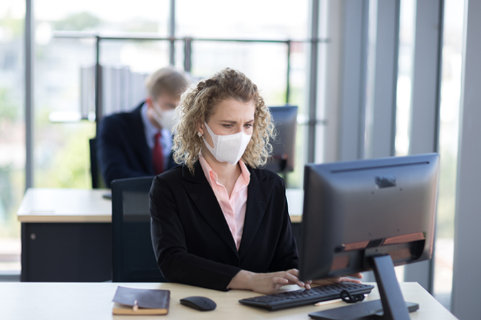 a photo of a lady working at a computer wearing a face mask in an office setting