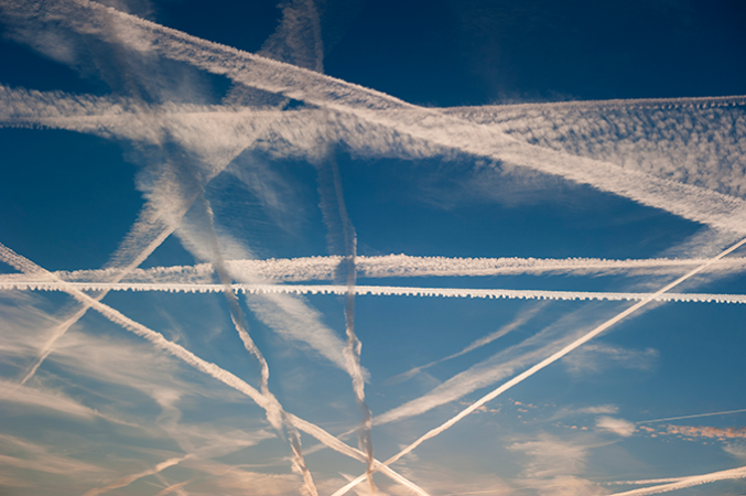 a photo of  jet contrails criss-crossing a blue sky