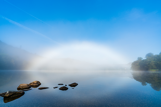 a fogbow over a lake