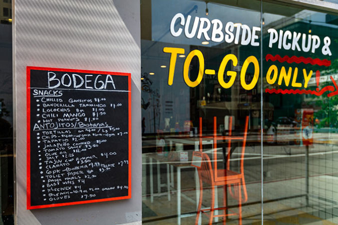 a photo of a restaurant closed for business during the COVD-19 pandemic, with a menu of things available for curbside pickup