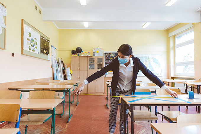 a photo of a masked teacher measuring distance between desks with her arms