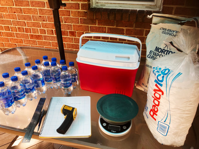 a photo of a cooler, some water bottles, salt, ruler, plate and notebook on a table ready for the experiment