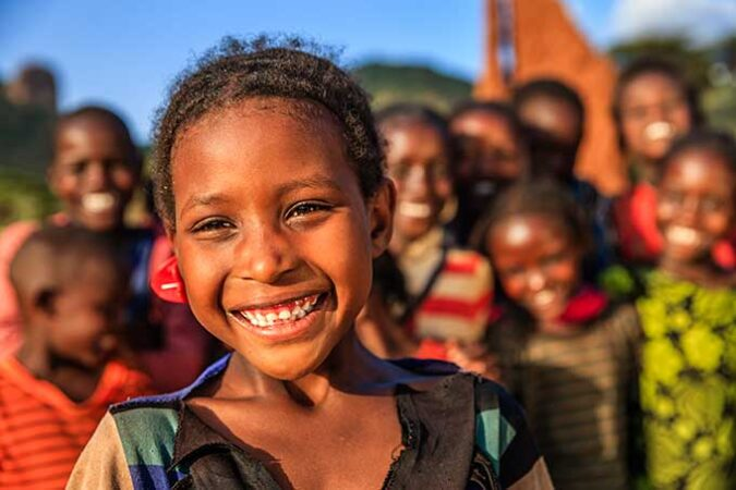 a photo of Ethiopian kids smiling at the camera in bright sunshine