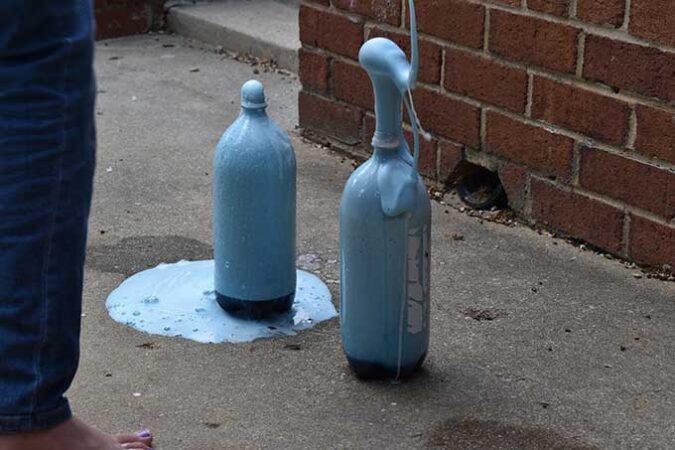 blue foam erupts from the 100 gram baking soda bottle volcanoes