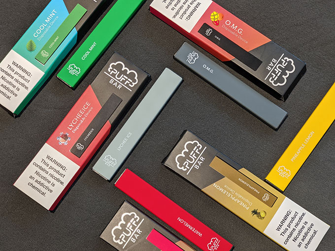 a photo of assorted Puff Bars (an e-cigarette) on a black background