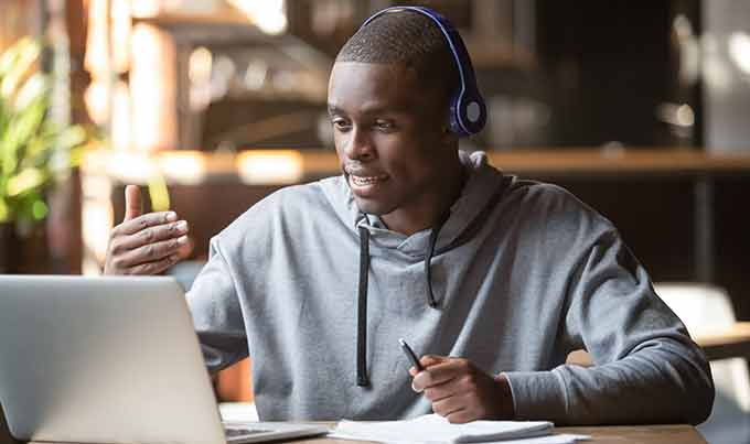 a young Black man wearing headphones mentoring over video chat