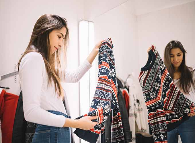 a woman considering buying a sweater in a store