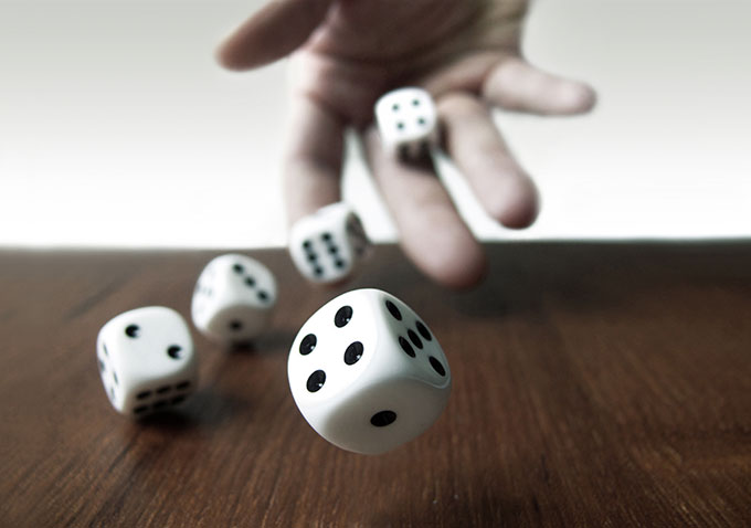a photo of a hand tossing dice onto a table
