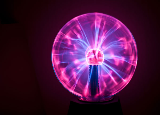 a photo of a plasma ball lit up with blue and purple plasma