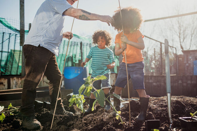 a photo of some kids gardening with a grandparent