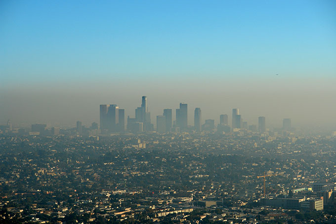a photo of downtown LA from a distance, brown smog sits over the city