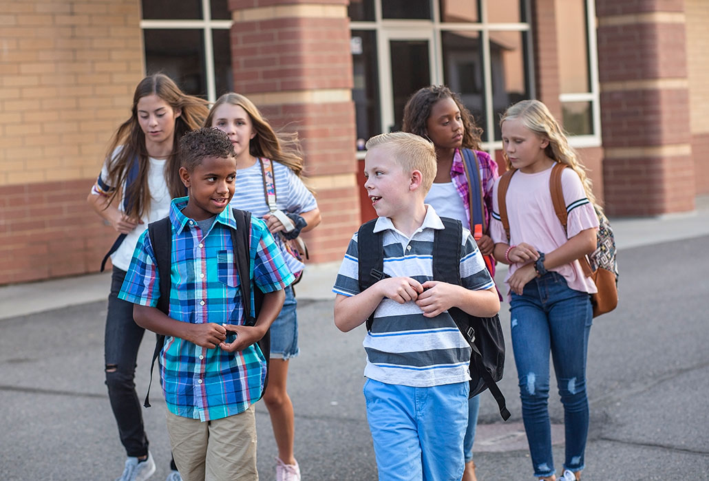a group of diverse kids outside a school
