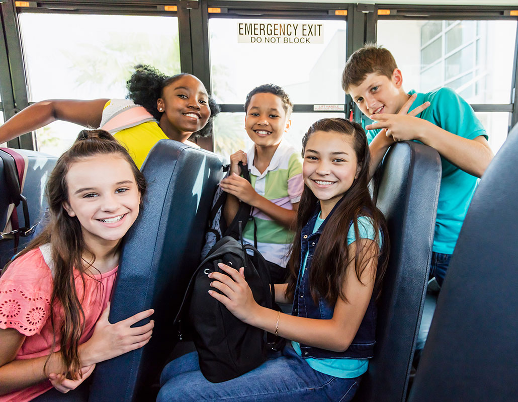 a group of diverse middle school kids on a bus