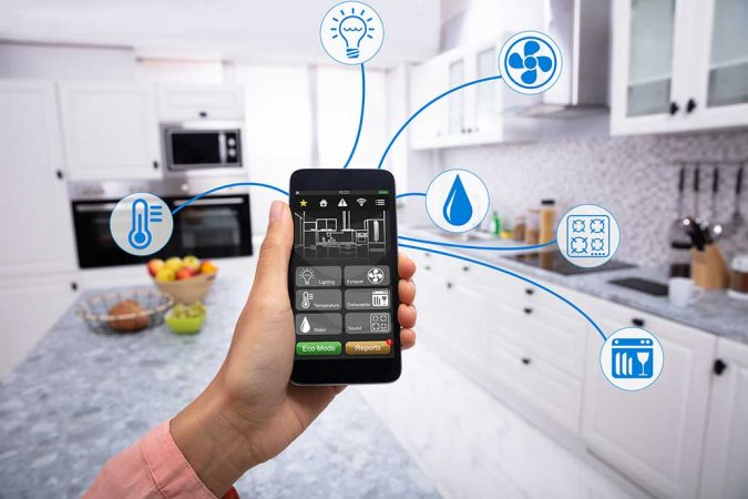 a picture of a hand holding a phone that can control various things in the room behind it