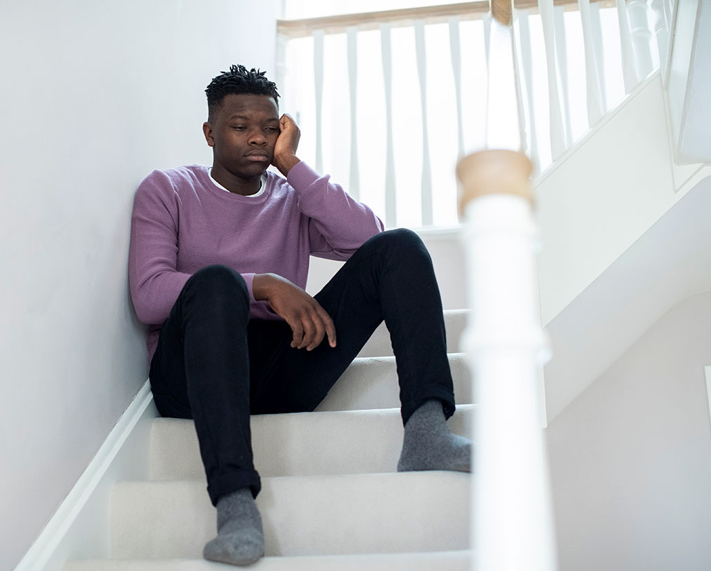 a young Black teen sits on stairs and stares into space