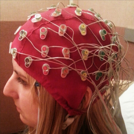 a woman wearing an EEG cap covered in sensors