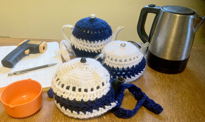 a set of three teapots and their cozies