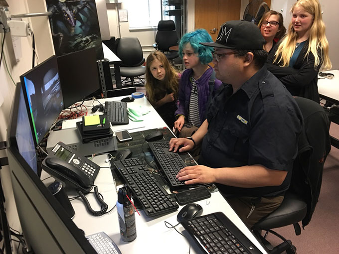 a man sitting at a desk playing video games with four onlookers
