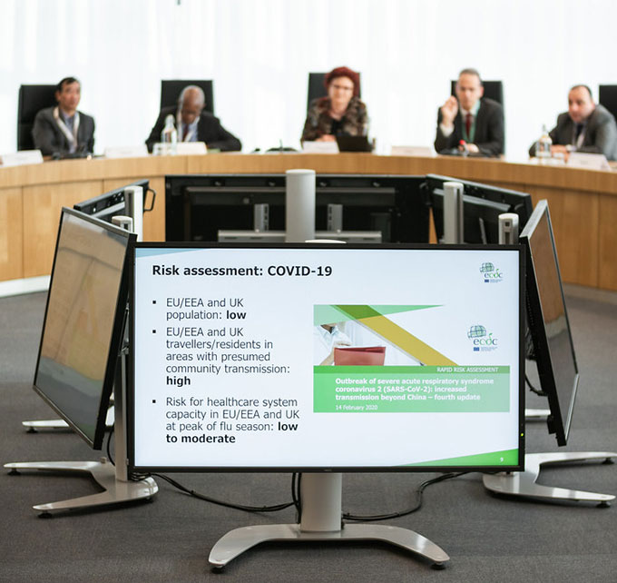 a photo of people sitting at a curved table behind monitors showing COVID-19 prediction data
