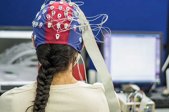 a woman sitting in front of the viewer wears an EEG cap