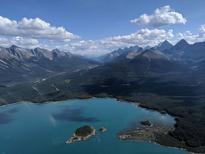 an aerial view of a pristine lake surrounded by mountains