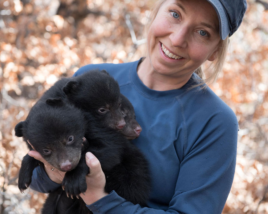 Heather Johnson holds two baby black bears and smiles