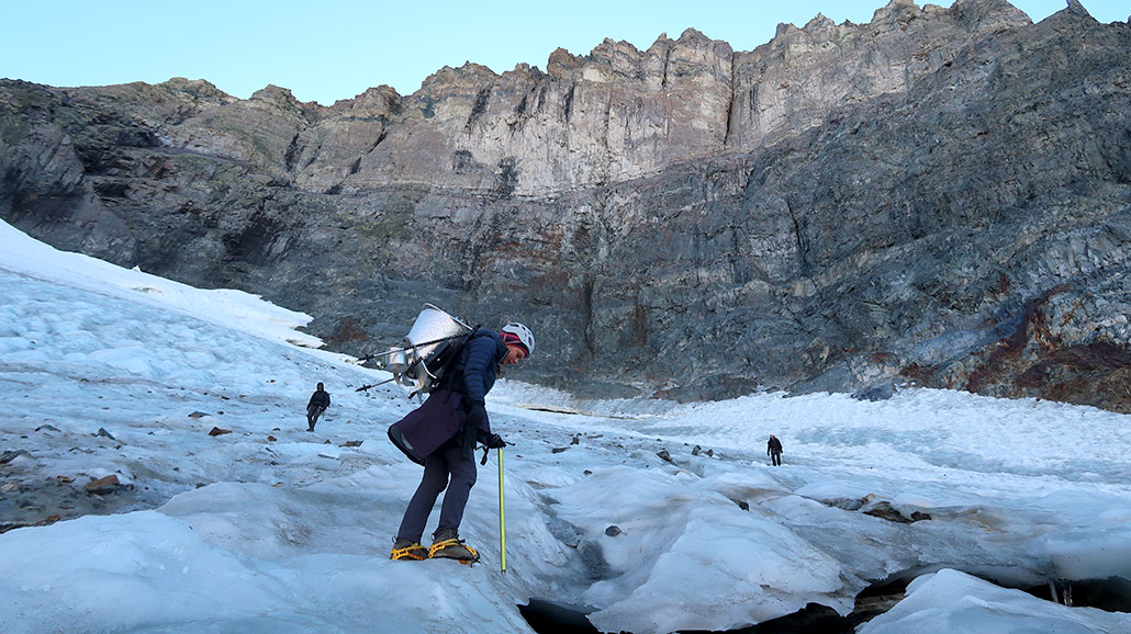 a photo showing a large rock shelf with the Dana glacier sitting underneath. Ellery is in the foreground.