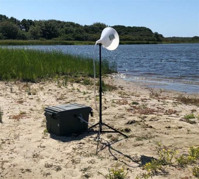 a photo of an air sampler on the shore of a pond