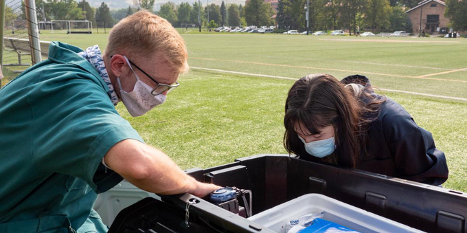 two people check a wastewater monitoring station on a field at the University of Colorado Boulder campus