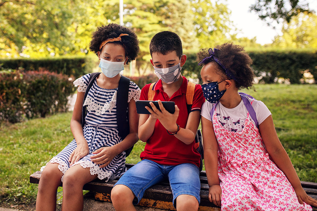 three masked student friends sitting together outside and looking at phone together