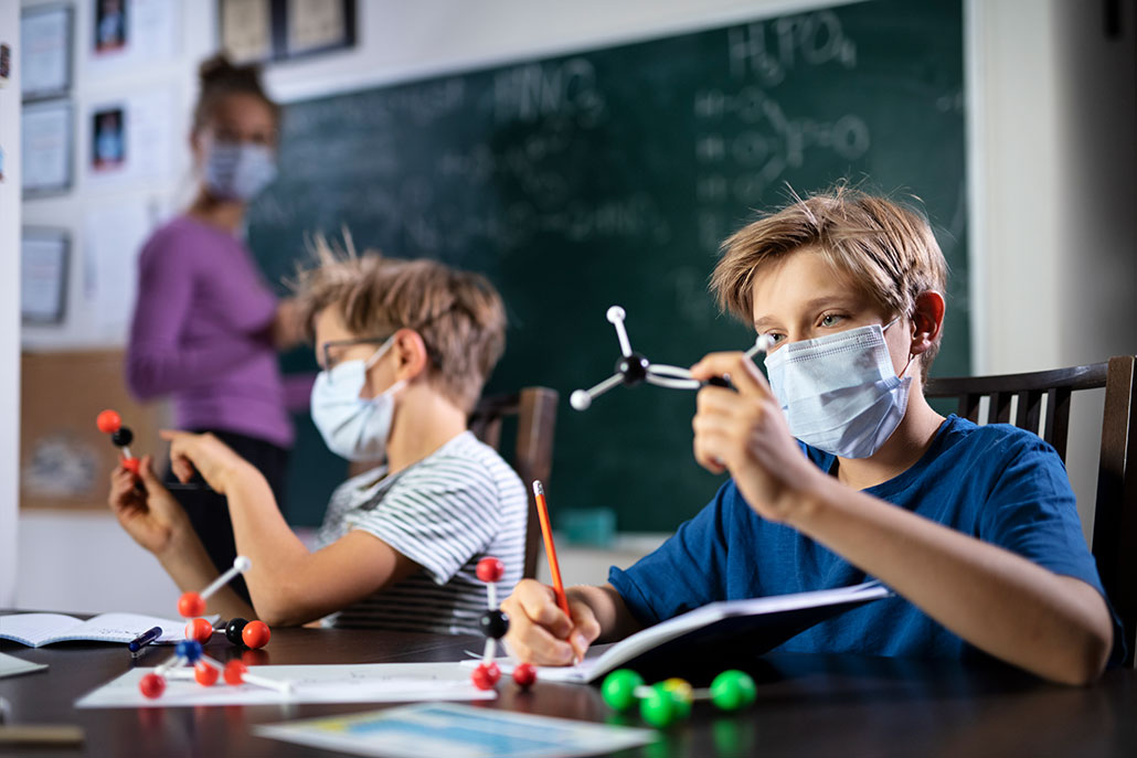 two boys look at molecular models and a teacher writes on a chalkboard behind them