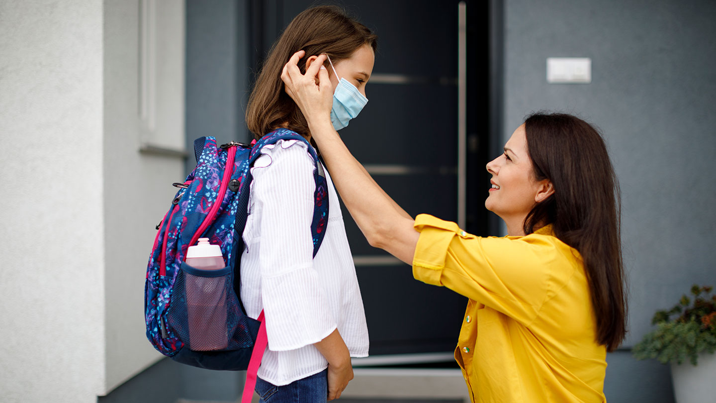 a mother putting a disposable paper mask on her daughter on the first day of school