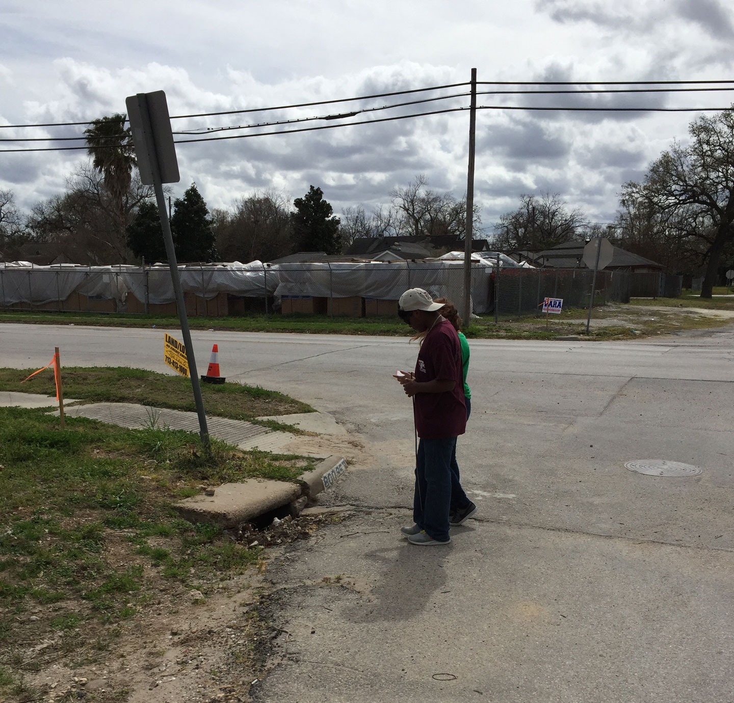 two high school students look at a storm drain