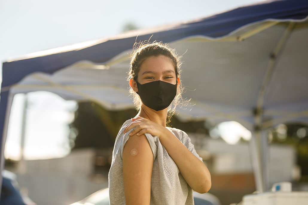 a girl standing outside showing a bandaid on her upper arm and wearing a face mask