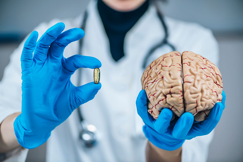 a scientist holds up a pill and a model of the human brain