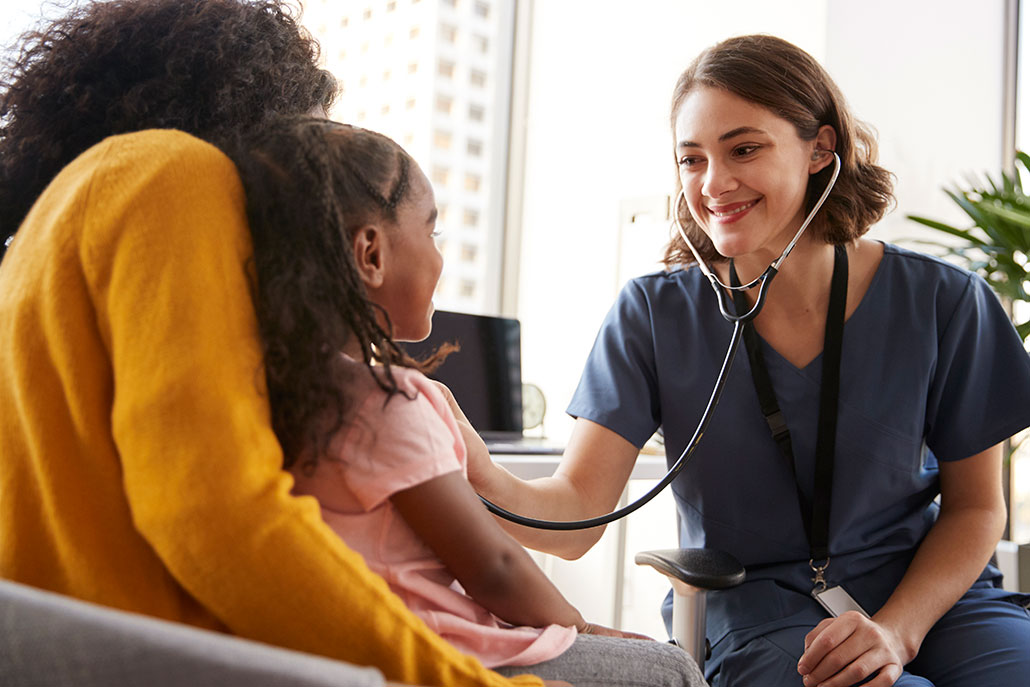 a doctor holds a stethoscope up to a young female patient